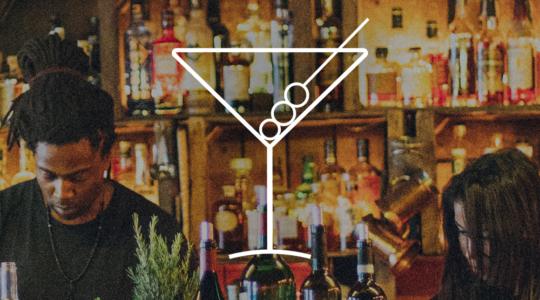Männliche und weibliche Bedienung hinter einer Theke, auf der Theke stehen einige Weinflaschen, im Hintergrund eine große Anzahl an Spirituosen. Auf dem Foto ist ein Martiniglas als Symbol platziert