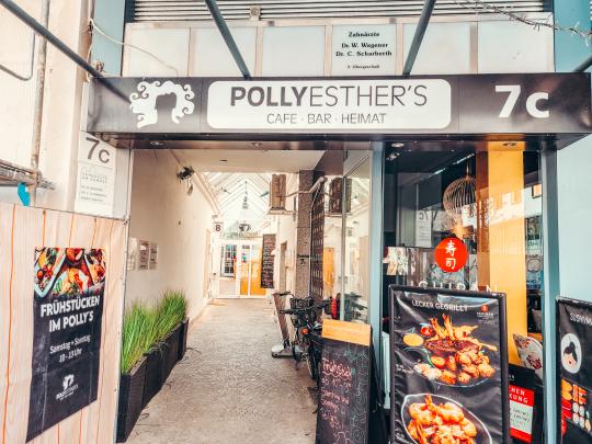 Burger mit Salat, Tomate und Käse auf Holztisch, darüber das Symbol eines Burgers