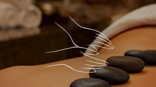 Frau liegt bei einer Massage und hat warme Steine über die Wirbelsäule verteilt liegen. Über dem Foto liegt ein Symbol von zwei massierenden Händen