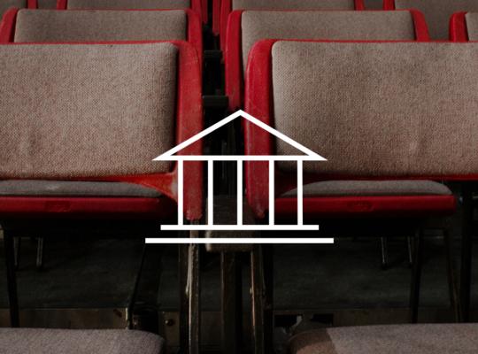 Mehrere Reihen roter Stühle. Davor ein Symbol, welches ein Theater symbolisiert.