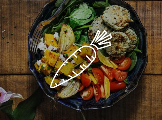 Teller mit Tomaten, Süßlkartoffeln, Blattspinat und Falafel darüber eine Symbol einer Karotte