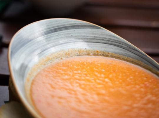 Suppenteller in Form einer Muschel, darin eine Tomatensuppe