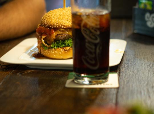 Cheeseburger auf Teller, davor ein Glas Cola, alles auf rustikalem Holztisch