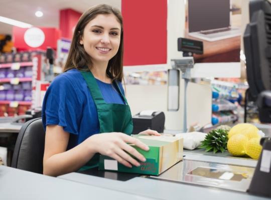 Potrait einer lächelnden Kassiererin im Supermarkt
