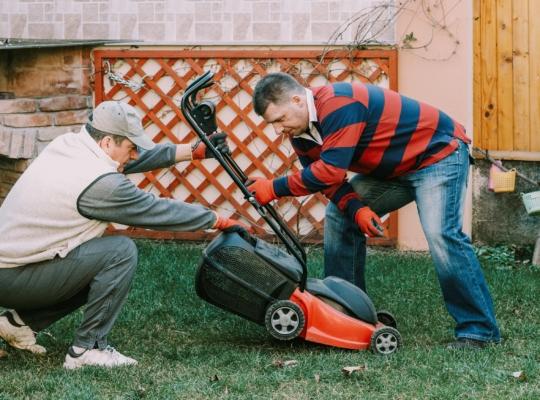 Zwei männliche Nachbarn im Garten, einen Rasenmäher reparierend