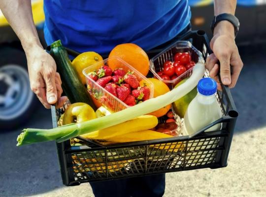 Mann mit Korb mit Lebensmitteln in der Hand
