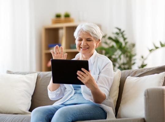 Ältere Frau mit Tablet in der Hand winkt in die Kamera