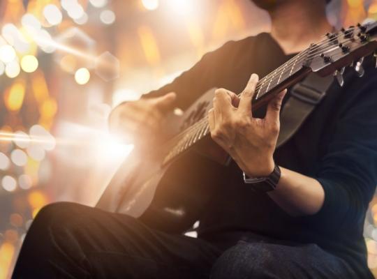 Gitarist sitzt mit seinter Gitarre auf einer Bühne