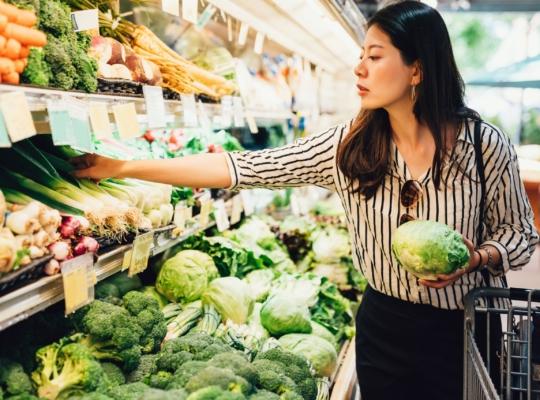 Frau mit Einkaufskorb im Lebensmittelgeschäft