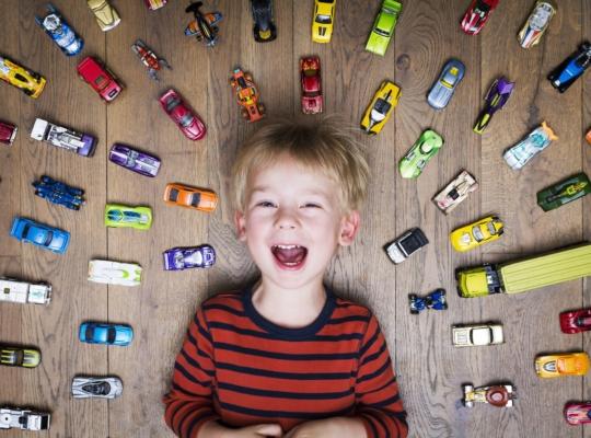 Kleiner Junge liegt lächelnd auf dem Boden mit vielen Spielzeugautos im ihn herum