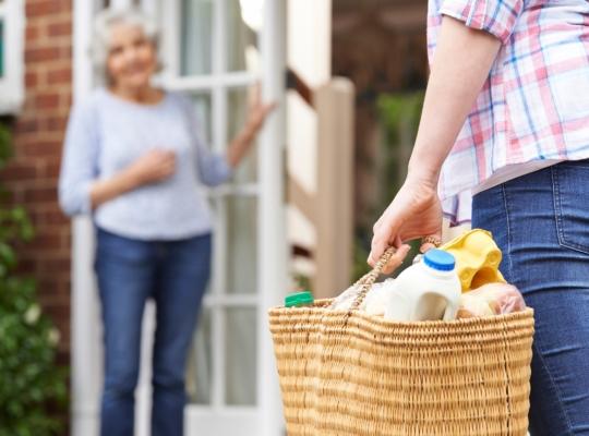 Frau trägt Nachbarin ihren Einkauf in die Wohnung