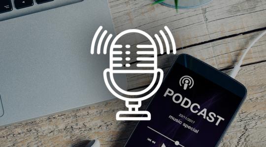 Handy mit Podcastapp, weißen Kopfhörern und Laptop daneben