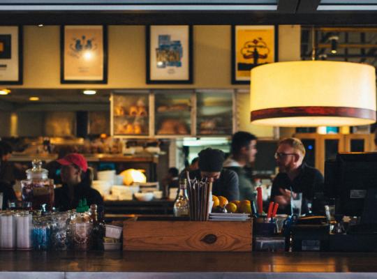 Theke einer Bar, dahinter sitzen Menschen an Tischen und unterhalten sich