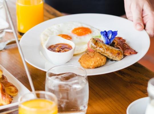 Tisch mit Brötchen, Crosaints, Saft, Kaffee und Teller mit Aufschnitt