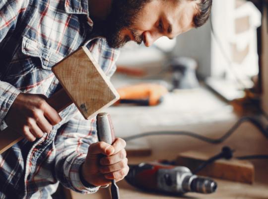 Mann arbeitet mit Hammer und Meißel in einer Holzwerkstatt