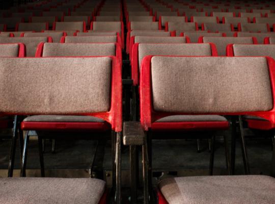 Mehrere Reihen roter Stühle