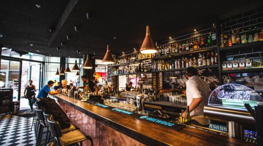 rustikale Theke der Bar aus dem Bulldog, Bedienung dahinter unterhält sich mit Gästen