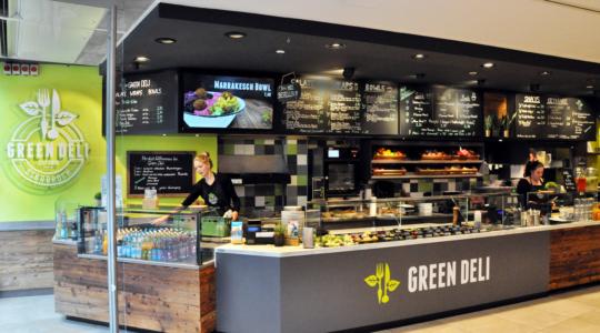 Verkaufstheke des Green Deli. Zwei Verkäuferinen bereiten Gerichte zu