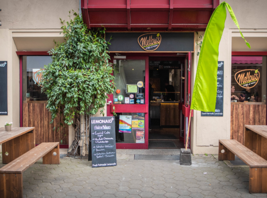 Eingang des Restaurants, davor Holztische und Bänke. An der Hauswand hängen Kreidetafeln auf den die Gerichte stehen.
