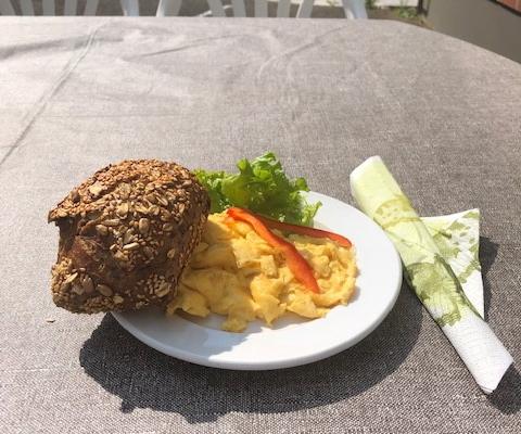 Teller mit Rührei, Vollkornbrötchen und Salatbeilage