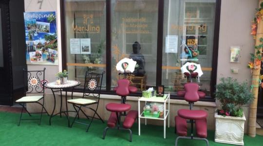 Eingang des Massage-Saloon, davor ein Tisch mit Stühlen sowie zwei Massagestühle