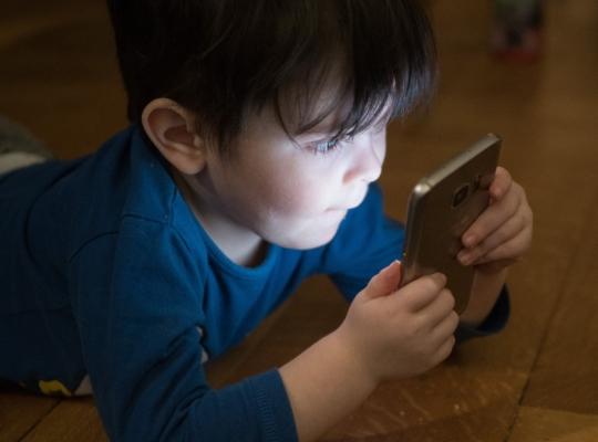 Kind auf Boden mit Smartphone in der Hand